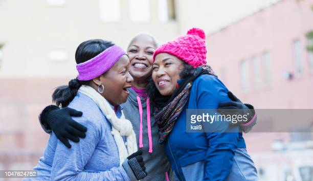 African-American women in city, laughing, hugging