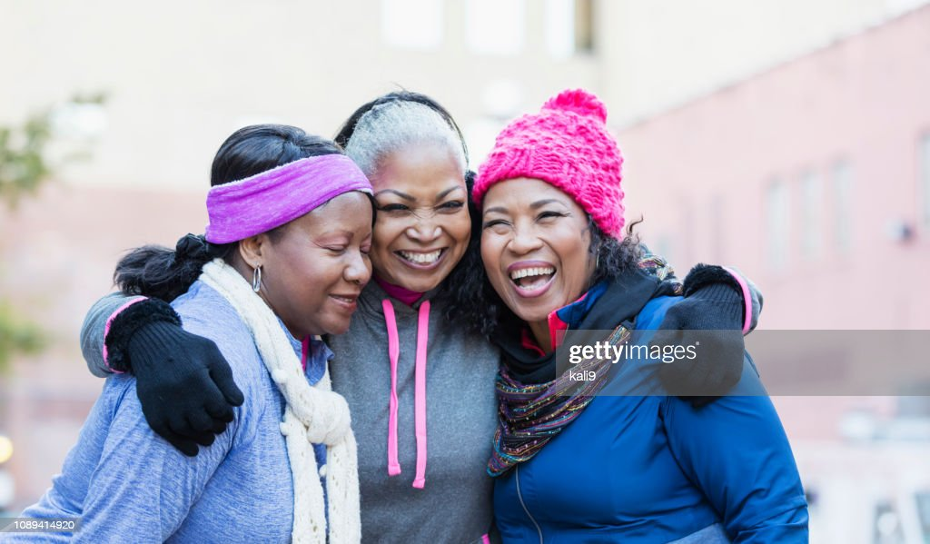 African-American women in city, laughing, hugging : Stock Photo