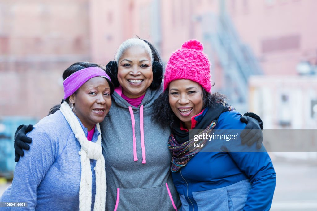 African-American women in city, smiling at camera : Stock Photo