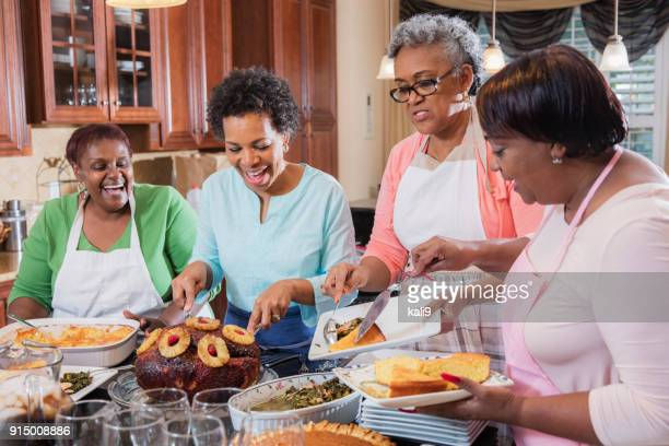 african-american women serving home cooked meal - african american family dinner stock photos and pictures