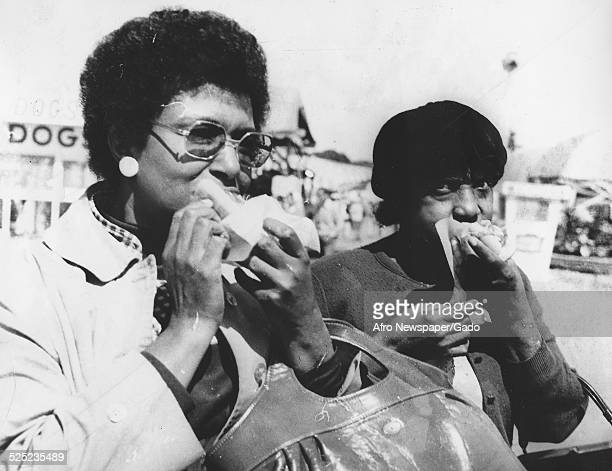 AfricanAmerican women wearing Afro haircut eating a meal at a State fair Richmond Virginia 1964 Original Caption Reads ' Olivia Dyson and Castoria...