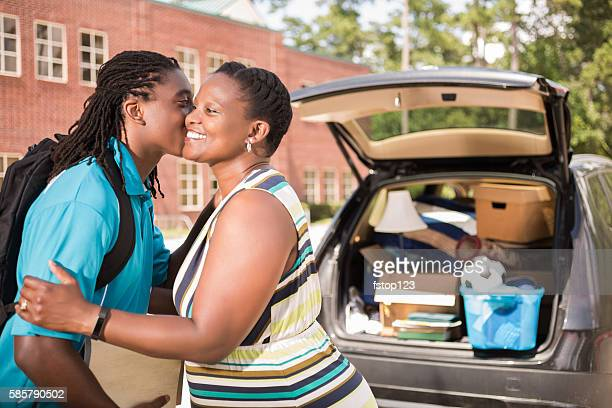 African-descent boy moves into college and kisses mom goodbye.