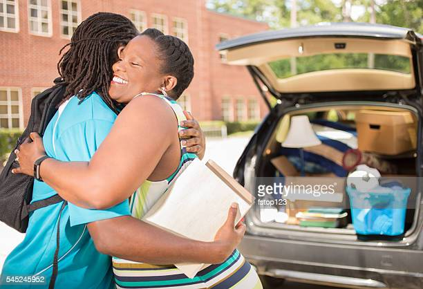 African-descent boy moves into college. Packed car, mother. School campus.