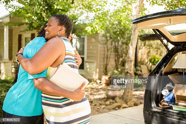 African-descent boy moves off to college.  Packed car, mom.  Hug.