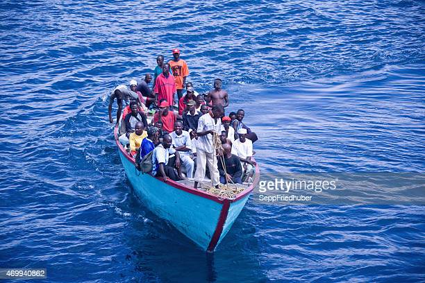 africans in an overloaded boat - refugee stock pictures, royalty-free photos & images