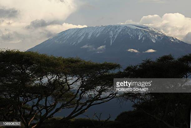 Africa's highest mountain Mt Kilimanjaro rises over a layer of clouds late afternoon on December 13 2009 According to a recent study by the journal...