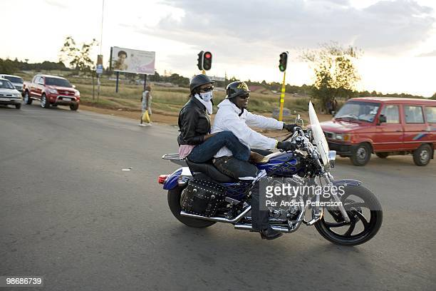 Afrika Tau age 31 rides with a friend on his Harley Davidson motorcycle on March 8 2009 in Soweto South Africa He grew up in Soweto and he is now a...