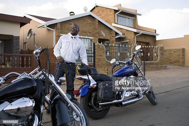 Afrika Tau age 31 waits to pick up a friend with his Harley Davidson motorcycle on March 8 2009 in Soweto South Africa He grew up in Soweto and he is...