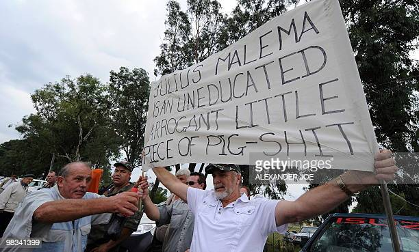 "Afrikaner Resistance Movement supporters hold a banner reading ""Juilius Malema is an uneducated arrogant little piece of pig-shit"" as they wait..."