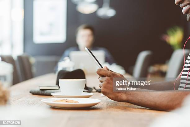 Afro amercian man using digital tablet in coffee shop