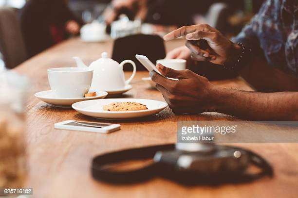 afro amercian man using smart phone in coffee shop - pointing at camera stock photos and pictures