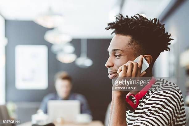 Afro amercian young man talking on mobile in coffee shop