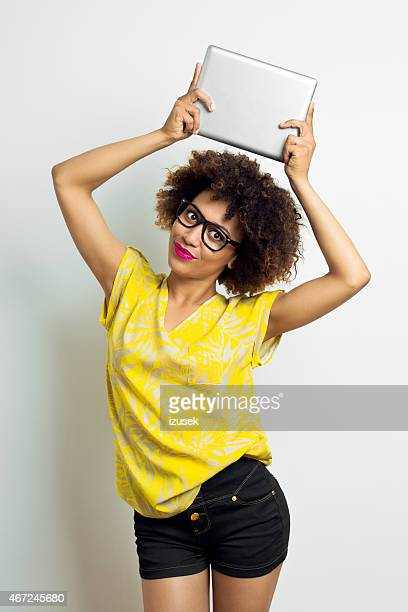 Afro Amercian Young Woman holding digital tablet above her head