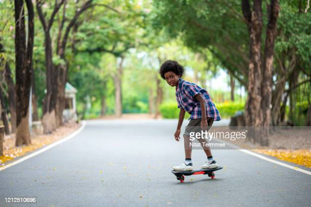 afro american boy skateboarding down a path in a public park. boy learning skateboard to play by self. - simple living stock pictures, royalty-free photos & images