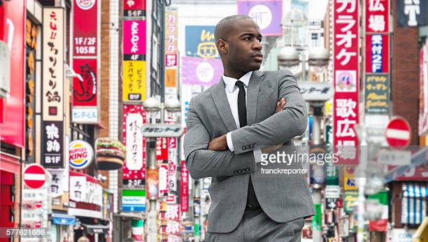 afro american businessman standing with arm crossed in shibuya