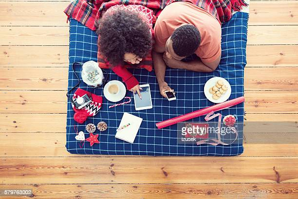 Afro american couple lying on bed and using technologies