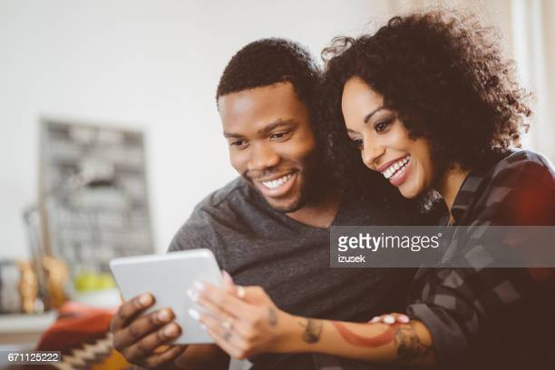 afro american couple using a digital tablet at home - izusek stock pictures, royalty-free photos & images