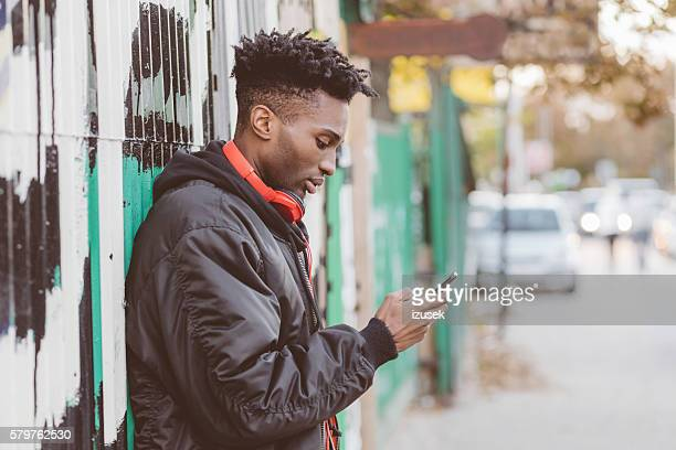 afro american guy using smart phone on the street - bomber jacket stock pictures, royalty-free photos & images