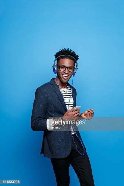 Afro américain homme avec le casque à l'aide de smartphone