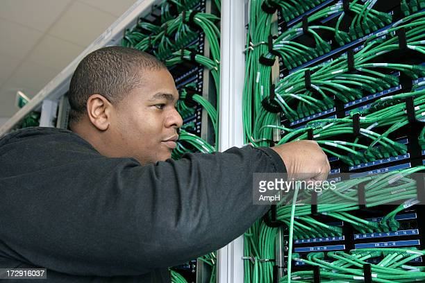 Afro american It worker plugs in a Cable