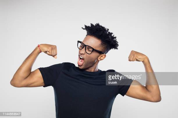 afro american man flexing arms - flexing muscles stock pictures, royalty-free photos & images