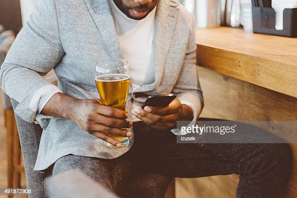 Afro american man sitting in the pub, using smart phone