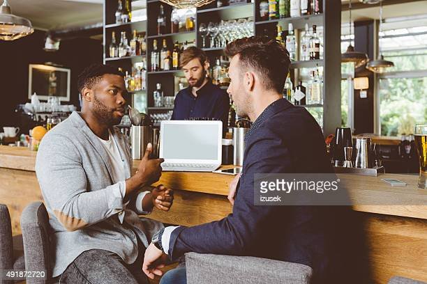 Afro american man talking with colleague in pub, using laptop