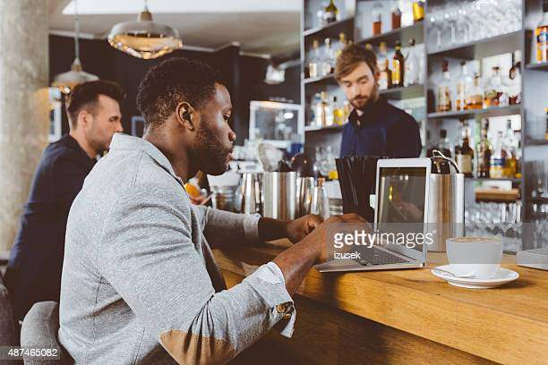 afro american man using laptop in a pub - incidental people stock pictures, royalty-free photos & images