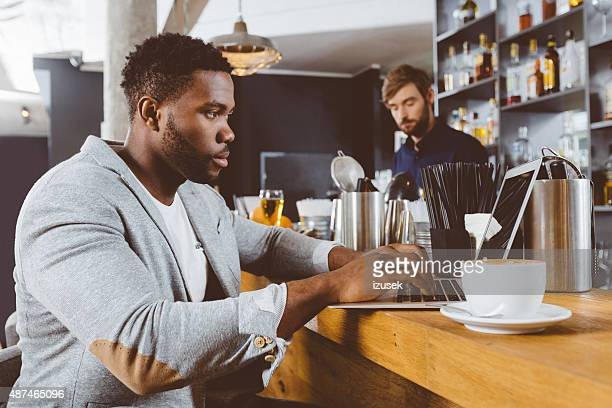 afro american man using laptop in a pub - izusek stock photos and pictures