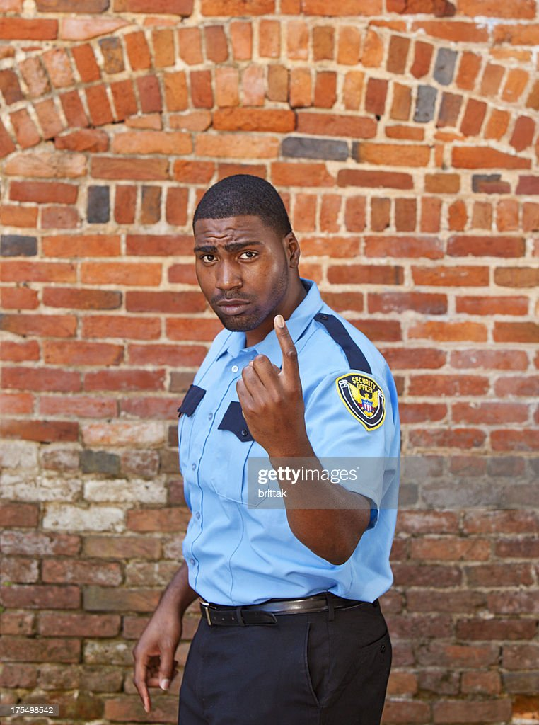 Afro american Security officer beckoning in front of brick building. : Stock Photo
