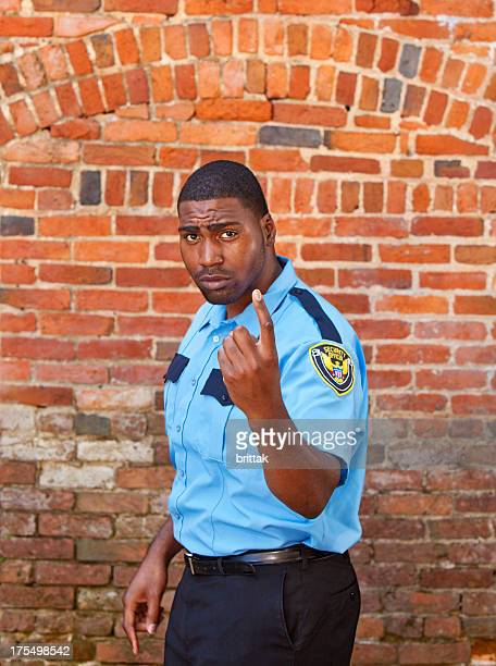 Afro american Security officer beckoning in front of brick building.