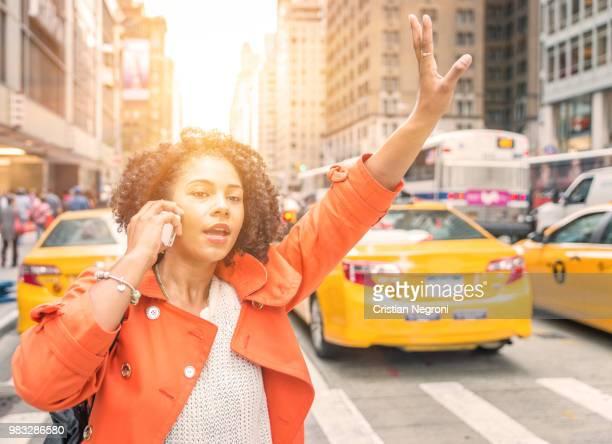 afro american woman calling a taxi in new york near time square district. - cristian neri foto e immagini stock
