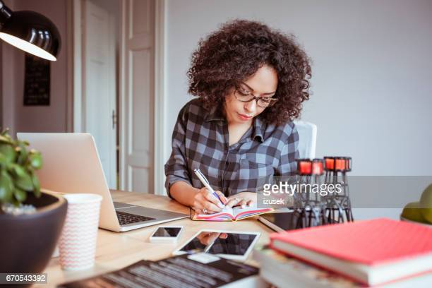 Afro american woman in a home office taking notes