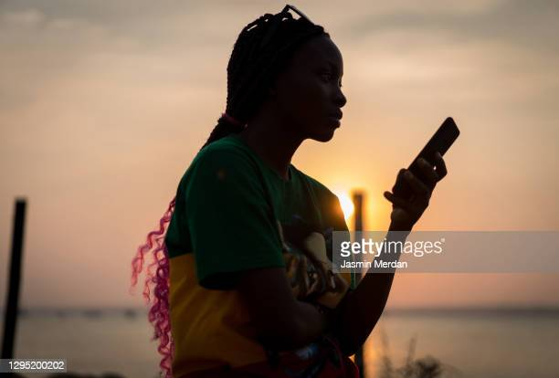 afro american woman sitting on shore using a mobile phone at sunset - native african girls stock pictures, royalty-free photos & images