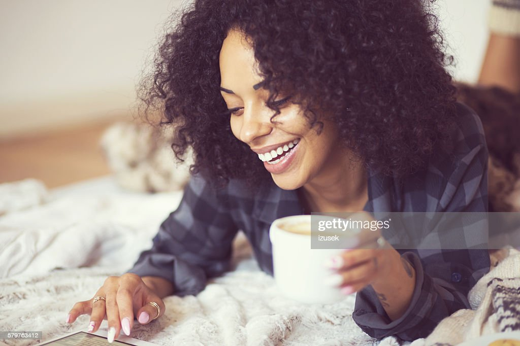 Afro american woman using a digital tablet at home : Stock Photo