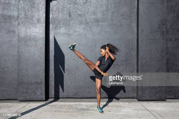 afro american woman with dreadlocks in a great athletic shape working out and training hard outdoors - kicking stock pictures, royalty-free photos & images