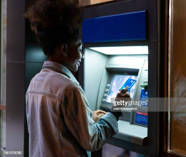 afro american woman withdrawing money at the atm - bank stock pictures, royalty-free photos & images