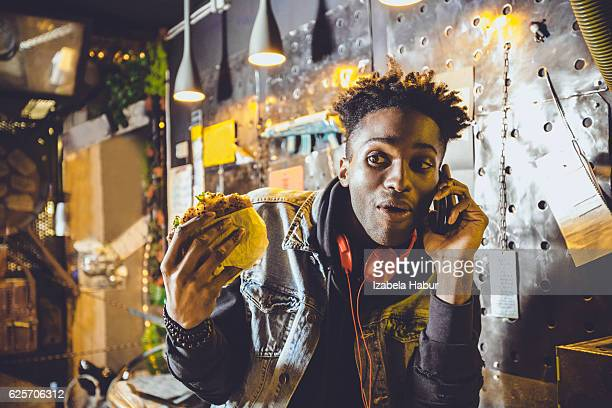 Afro american young guy eating burger in pub