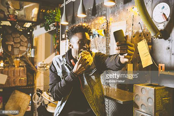 Afro american young guy eating burger in pub, taking selfie
