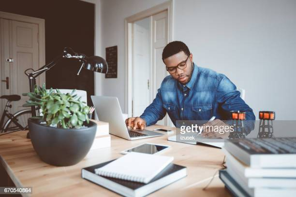 afro american young man working at home office - authors foto e immagini stock