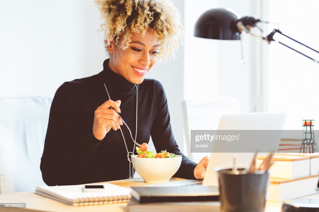 Afro american young woman eating lunch at the desk : Stockfoto