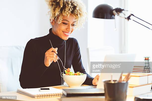 afro american young woman eating lunch at the desk - almoço imagens e fotografias de stock