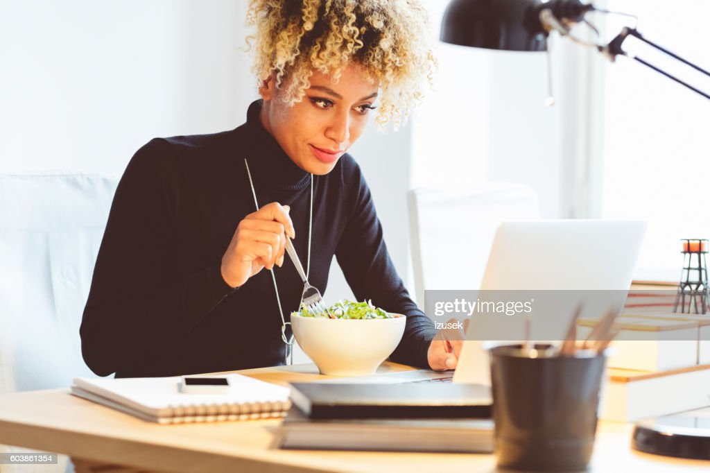 Afro american young woman eating lunch at the desk : Stock Photo