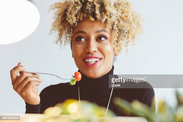 Afro american young woman eating salad
