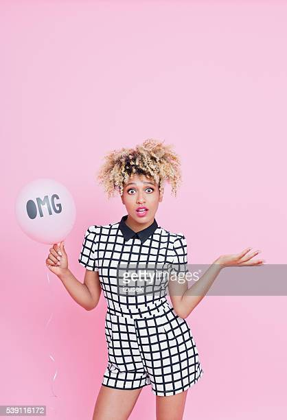 Afro American young woman holding balloon with OMG sign