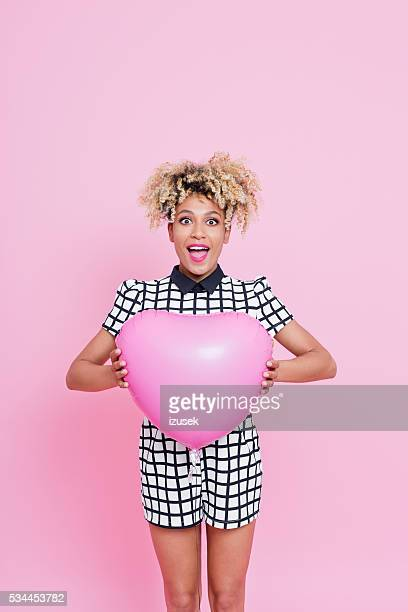 Afro American young woman holding pink heart shaped balloon