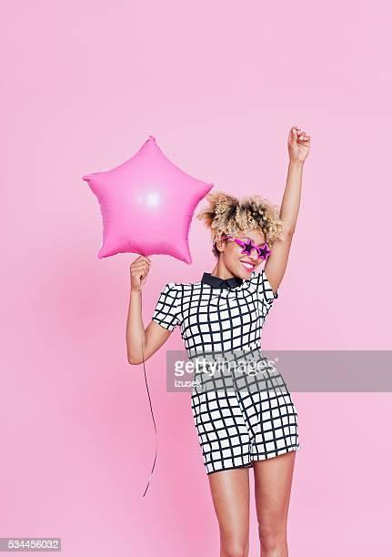 Afro americano joven mujer sosteniendo rosas estrella de aluminio de globos aerostáticos