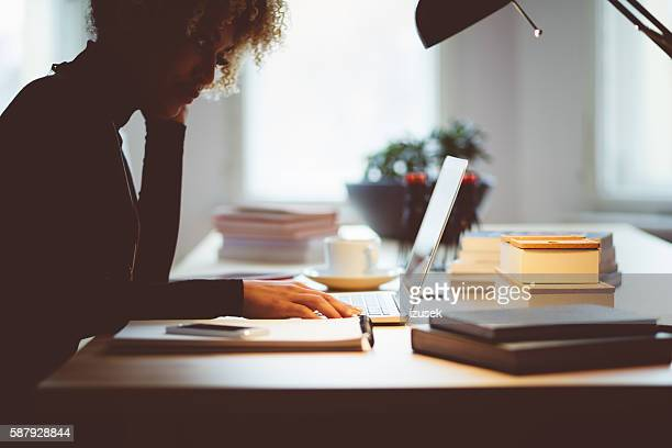 Afro american young woman using a laptop in an office