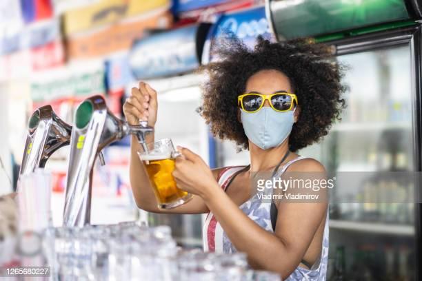 afro barkeeper mit schützender gesichtsmaske gießt bier aus einem wasserhahn in einer sommerbar - corona beer stock-fotos und bilder