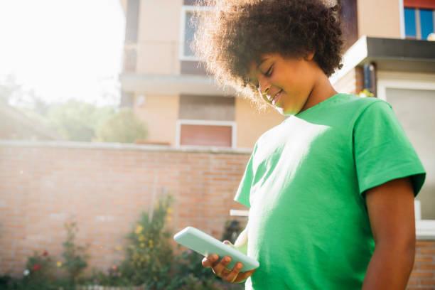 Afro boy using smart phone in back yard
